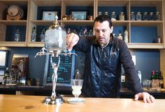 Lawrence Cary, owner of North Coast Distilling, pours a glass of absinthe inside his Astoria tasting room.