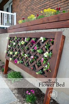 Hide the ugly retaining wall in your yard with a beautiful vertical flower bed - It looks great! Something like this might do well in front of pop's house...Krissy :)