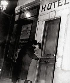 A Paris side street as it lives in the imagination of movie directors and romantic people: the little hotel entrance, the gas lamp in the corner, and an embracing couple.     from Paris: City of Kisses,1938 by Lucien Aigner