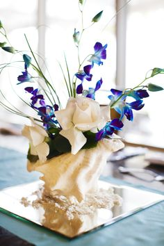 Conk shell centerpieces using the blue orchids and roses..