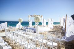 Beach wedding. The flowing white fabric is an elegant way to embrace the wind
