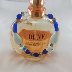 Superbe bracelet argenté perles bleu pacifique facettées,2 perles cubiques porcelaine fleurie, 2 feuilles blanches porcelaine,8 fleurettes