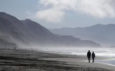 Visitors walk along the beach at Fort Funston