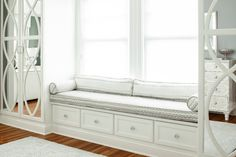 Master bedroom with floor to ceiling mirrored wardrobes flanking built-in window seat with white and gray zigzag fabric cushions under windows dressed in white roller shades.