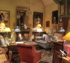 Country sitting room with comfortable chairs a roaring fire and pictures everywhere