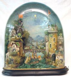 LARGE 19TH CENTURY AUTOMATA, featuring a castle turret with revolving sentry opposite a windmill with a train moving between the two over a three masted sailing ship moving in choppy seas supported upon a turned rounded ebonised wooden base and under a glass dome.