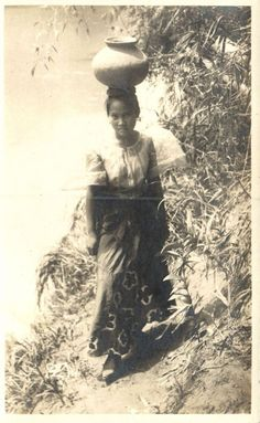 A beautiful Filipina fetching water. Early 1900