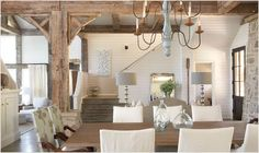 French country.  Exposed wood beams and column.  Charming table with comfy chairs.  Stair landing.  Chandelier.  Exposed brick.  Shabby chic.  White horizontal wood paneling.