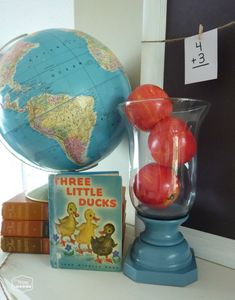 back to school mantel with vintage globe, vintage books, hurricane with apples, flash cards, chalkboard at thehappyhousie