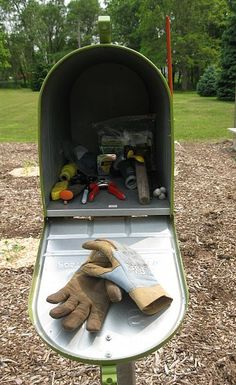 Coolest idea yet.....  Mailbox in the garden to hold gloves and tools. Keeps things dry and clean and right where you need them. Could make that so cute.