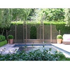 Nice example of treillage accent/focal point against hedging near pool. Outdoor privacy screen trellises at HomeInfatuation.com.