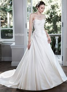 Shimmer satin A-line wedding dress with an asymmetrical pleated bodice, accented with sparkling Swarovski crystal embellishment at the hip. Sareya by Maggie Sottero.
