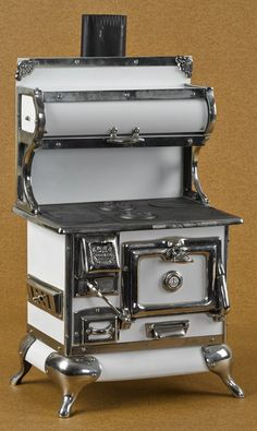 Reproduction Karr Range Co. cast iron, nickel, and tin toy stove, 21'' h., 12 1/2'' w.
