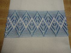 This white huck towel is 14 x 22. Its stitched with light blue pearl cotton. Swedish weaving or huck weaving was popular back in the 1930s and 1940s. It was done on huck fabric which is 100% cotton. The right side of the fabric has a pattern of double loops of thread called