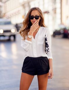 {Street style} | White button up blouse, black leather shorts, black and white printed clutch.