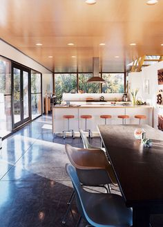 """""""It was a major decision to put the kitchen in the center where everything would revolve around it,"""" says Lazor. """"We did this simply by following what patterns we observed—it was just where people gravitated."""" The bar stools are by Blu Dot, and the chairs by Charles and Ray Eames.  Photo by: Chad Holder"""