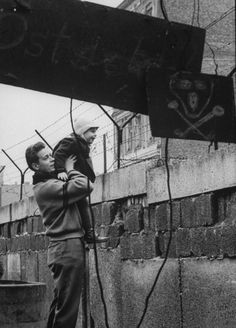 German showing a child the other side of the Berlin Wall - January 1961