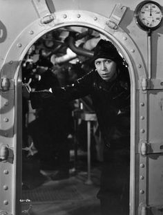 1940: A sou'wester-clad George Formby peers out of an engine room in a British spy film which also stars Phyllis Calvert, Garry Marsh, Romney Brent, Bernard Lee, Coral Browne.The film is the musical comedy 'Let George Do It' (1940) from Ealing Studios, Director: Marcel Varnel (Photo by Hulton Archive/Getty Images)