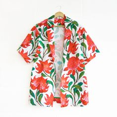 This jacket is a relaxed a-line style featuring original 'Big Red Waratahs' print from the Alter Native collection.Mid length sleeves, revere collar and invisible front button closure to wear open or closed.Made from digitally printed 100% cotton. Dry clean or hand washable.Limited Edition. Made in Adelaide.