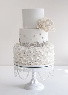 all white ruffles wedding cake with silver sugar pearls