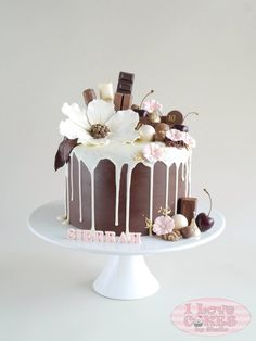 Drippy chocolate cake with beautiful flowers decorating the top.