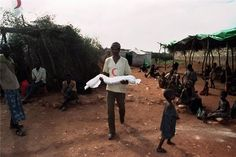 A Somali aid worker carries a dead child for burial in a Baidoa refugee camp December REUTERS-Yannis Behrakis Muammar Gaddafi, In Harm's Way, Refugee Crisis, Syrian Refugees, Somali, Human Emotions, African History, Albania, World History