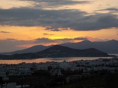 January sunset view of Chora from the mountain behind the town. Overlooking St. George bay and the Stelida with the island of Paros in the background.  photo by Ηλιασ