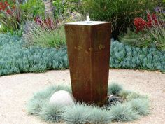 Fountains are an easy, low-maintenance water feature for gardens. This vertical copper-colored fountain takes center stage in a circular design featuring ornamental grasses and stones. www.deboracarl.com