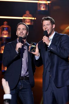 Jimmie Johnson Photos Photos - Professional race car driver Jimmie Johnson (L) and professional baseball player Clayton Kershaw speak onstage during the 2014 American Country Countdown Awards at Music City Center on December 15, 2014 in Nashville, Tennessee. - American Country Countdown Awards Show