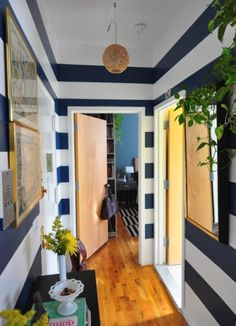 Major drama (the good kind) with wide blue and white striped walls in this entry hall from @Completely-Coastal.com