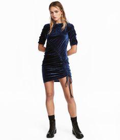 Mörkblå. En kort, figurnära klänning i krossad sammet med tvärgående dragsko. Klänningen har kort ärm med rynk. Ofodrad.