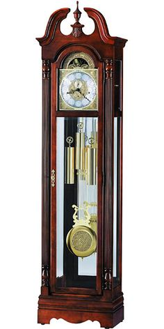 """This 77th Anniversary Edition floor clock features a delicately curved swan neck pediment which is crowned by a turned finial and decorative shell overlay.  The polished brass finished anniversary dial offers elaborate corner spandrels, a center disk with an astrological blue moon phase, and a silver chapter ring with applied brass Arabic numerals.  Size: H. 85-1/4"""" W. 22"""" D. 12-3/4"""""""