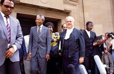 Johannesburg, South Africa, 1991/2. ANC leader Nelson Mandela leaves the Johannesburg High Court followed by his wife Winnie Mandela and lawyer and struggle icon  George Bizos during Winnie Mandelas trial for the murder of ANC child activist Stompie Sepei. She was not found guilty.Bizos famously defended Nelson during the Treason Trial