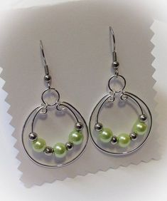 Double silver plated wire hoop design earrings with mint green pearly bead feature on surgical stainless steel ear wires. #JewelryIdeas