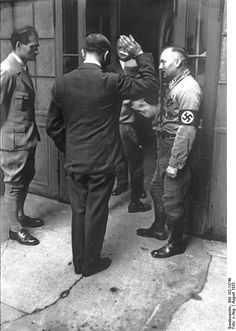 Shot from behind: The unmistakable figure of Adolf Hitler was caught in this unusual photo by an unknown photographer, who obviously missed his chance of a full-face picture of the would-be chancellor in 1932. To Hitler's left stands the ever dedicated Rudolf Hess. On the right is an unidentified SA officer. Occasion, location unknown.