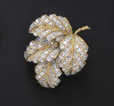 A FINE DIAMOND BROOCH, BY VAN CLEEF & ARPELS Designed as four overlapping circular-cut diamond leaves, enhanced by textured gold veining and stem, mounted in 18k gold and platinum, with French assay marks and maker's mark Signed Van Cleef & Arpels, no. 17.345 With maker's mark for Pery et Cie