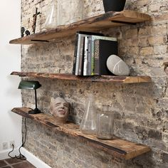 Rough wood shelving on a brick wall. Very rustic. Bedroom?