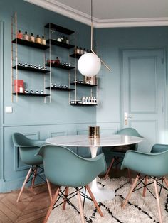 IC Lights hangs delicately in this modern dining room with a pale blue color palette and wood floors.