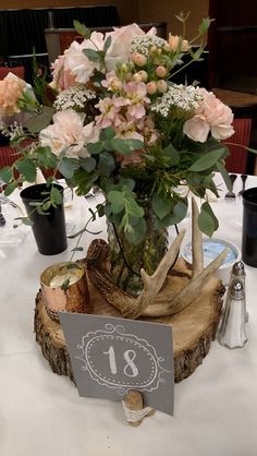 Rustic reception centerpiece peach flowers in hobnob jar on wood slice surrounded by deer antlers.