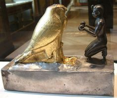 Tiharkah kneeling in obeisance to the falcon god Horus with an offering.