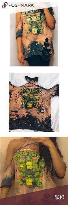 Distressed TMNT tee Vintage look/ distressed teenage mutant ninja turtles shirt....Handmade by me . Size large.Measures at 27 inches from shoulder to bottom. Halter style/off the shoulder design. Wearing a bandeau or cute bralette would look super cute underneath this item! Washing on gentle cycle is recommended. Lowball offers, apps outside of Poshmark,trades.... price is firm unless bundled. Happy poshing! Tops Tees - Short Sleeve