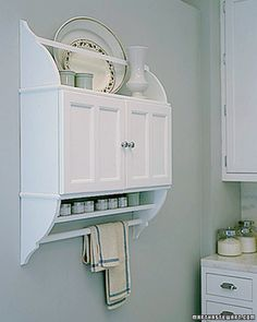 Mass-produced cabinets take on custom character with a few easy additions. Here, four matching brackets -- two right-side up, two upside down -- expand the usefulness of a double-door cupboard. A narrow shelf tucked underneath is the perfect spot for spices. Below it, a dowel between the brackets holds towels. On top, a flat horizontal strip keeps platters in place. Once painted, the multipart cupboard looks like a single piece of cabinetwork.