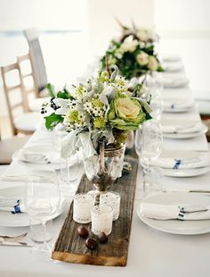 Using old wooden planks as alternative rustic table runners to create a warm and welcoming wedding reception