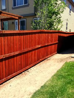 Refinished cedar fence stained with TWP Redwood.
