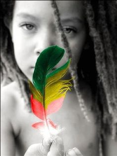 Beautiful child rocking the Rastafari colours, of red, gold and green, with dreads