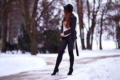 Szary płaszcz, skórzane legginsy, beżowy sweter i długie kozaki na obcasie