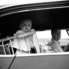 Dad's driving. open windows. playpen in the backseat. Vivian Maier