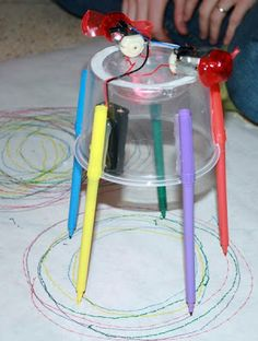 Drawing robots -- made from old containers and dollar store pens to make  and a weighted motor from dollar store handifans