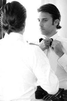 Gregg prepared for the big day in his groom's suite. He wore a tuxedo with a black velvet bow tie. #groom #weddingday Photography: Donna Newman Photography. Read More: http://www.insideweddings.com/weddings/elegant-all-white-wedding-at-the-breakers-in-florida/362/