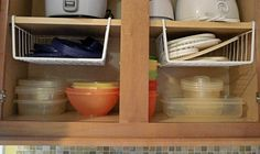 Hanging Shelf Dividers Hanging shelf dividers are also useful in taking advantage of empty space. I love this idea for smaller and lighter items, such as tupperware lids or plastic plates. Organiser Tupperware, Tupperware Storage, Tupperware Organizing, Small Kitchen Organization, Diy Kitchen Storage, Home Organization, Kitchen Hacks, Organized Kitchen, Organisation Hacks